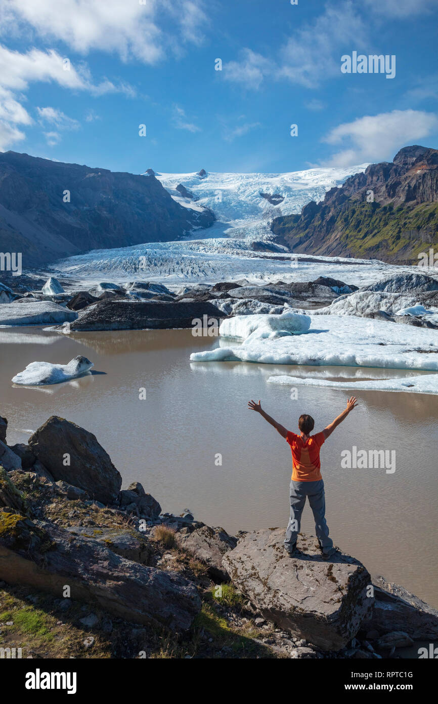 Person beside Kviarjokull glacier and moraine lake. Vatnajokull National Park, Sudhurland, south east Iceland. - Stock Image