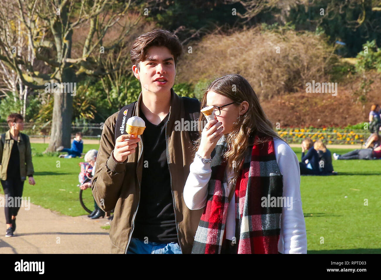A couple are seen eating ice cream on a warm and sunny day at St James's Park. The Met Office is predicting temperatures in the UK could break records this weekend, with high pressure from Europe bringing dry and sunny weather. - Stock Image
