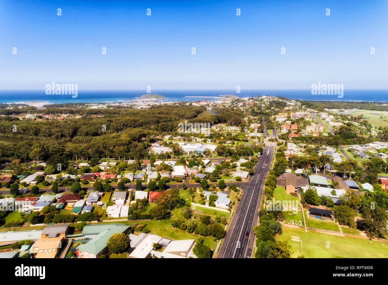 Aerial view over local regional town Coffs Harbour on Australian Middle North Coast of NSW towards Pacific ocean waterfront over local suburbs, street Stock Photo