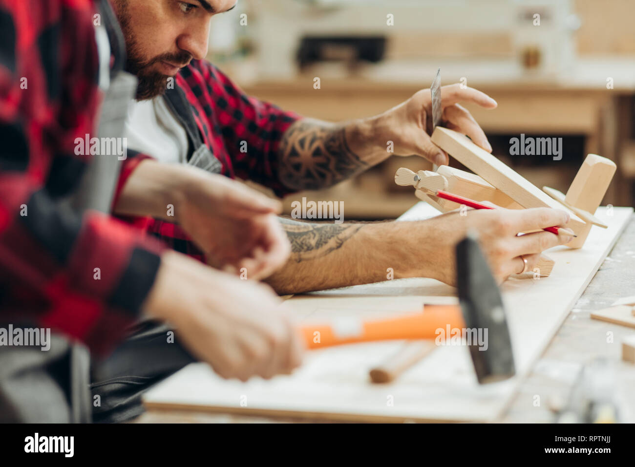 Young caucasian father and his pre-teen son working together in a wooden workshop, building a wooden bird house. Little boy dressed in apron and weari - Stock Image