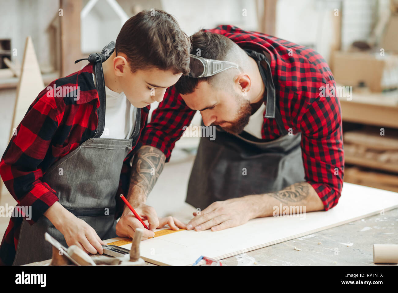 Curious little boy take classes of carpentery from famous woodworker. Hobby is growing into work by vocation. - Stock Image