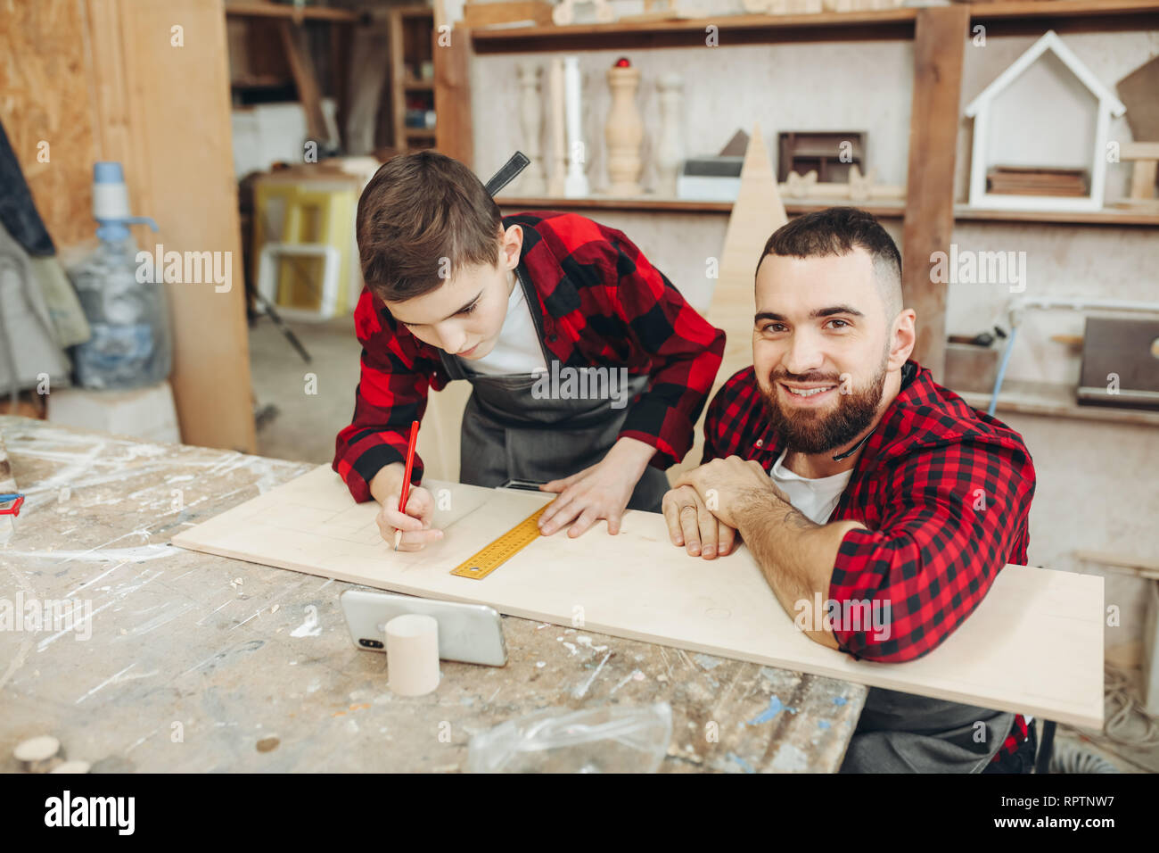 Caucasian man and caring father helping his concentrated pre-teen ager son to take measures of wooden plank in workshop during family masterclass of c - Stock Image