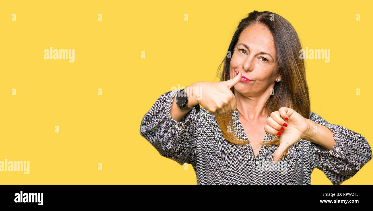 Beautiful middle age business woman Doing thumbs up and down, disagreement and agreement expression. Crazy conflict - Stock Image