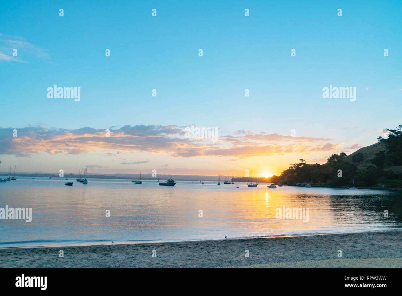 Scenic vista as sun sets over Pilot Bay on Tauranga Harbour with silhouette of boats and Mount Maunganui Stock Photo