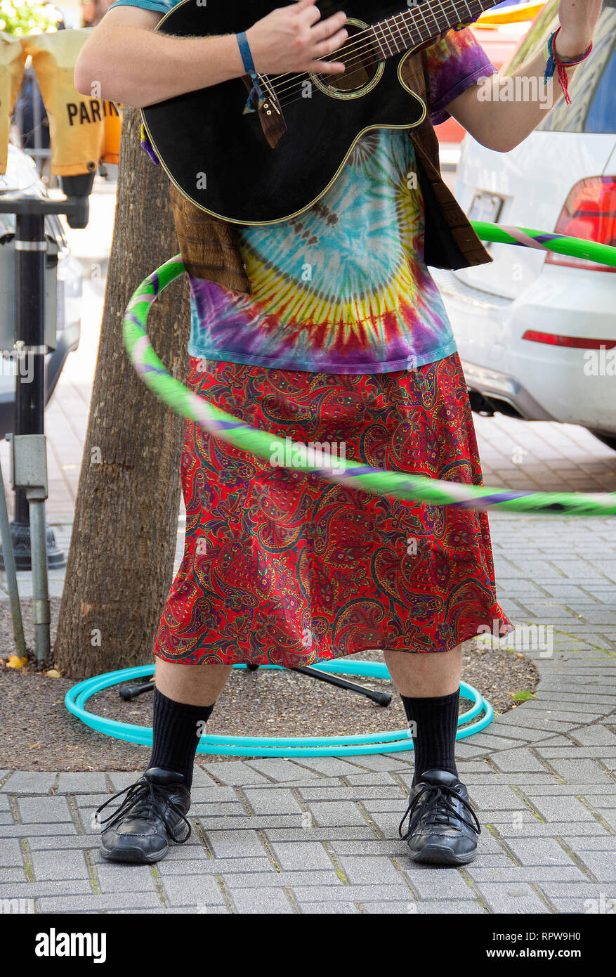 man wearing hippie style clothing playing guitar and twirling a hula hoop on street corner - Stock Image
