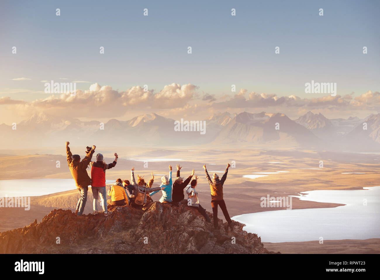 Large group of happy friends is having fun on mountain top and looks at mountain's valley. Adventure or travel concept Stock Photo