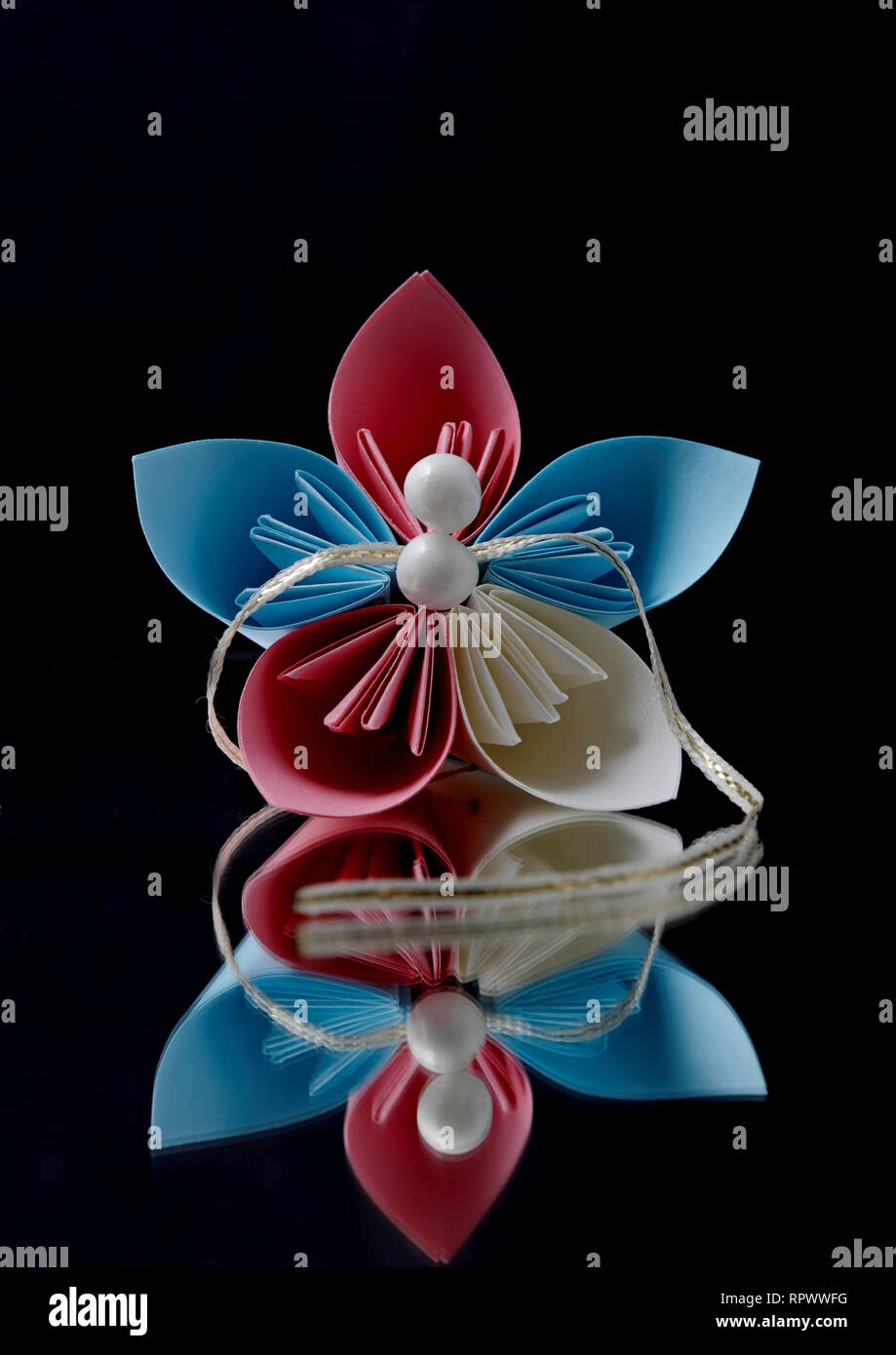 Beautiful red and blue origami flower and pearls on a black background Stock Photo