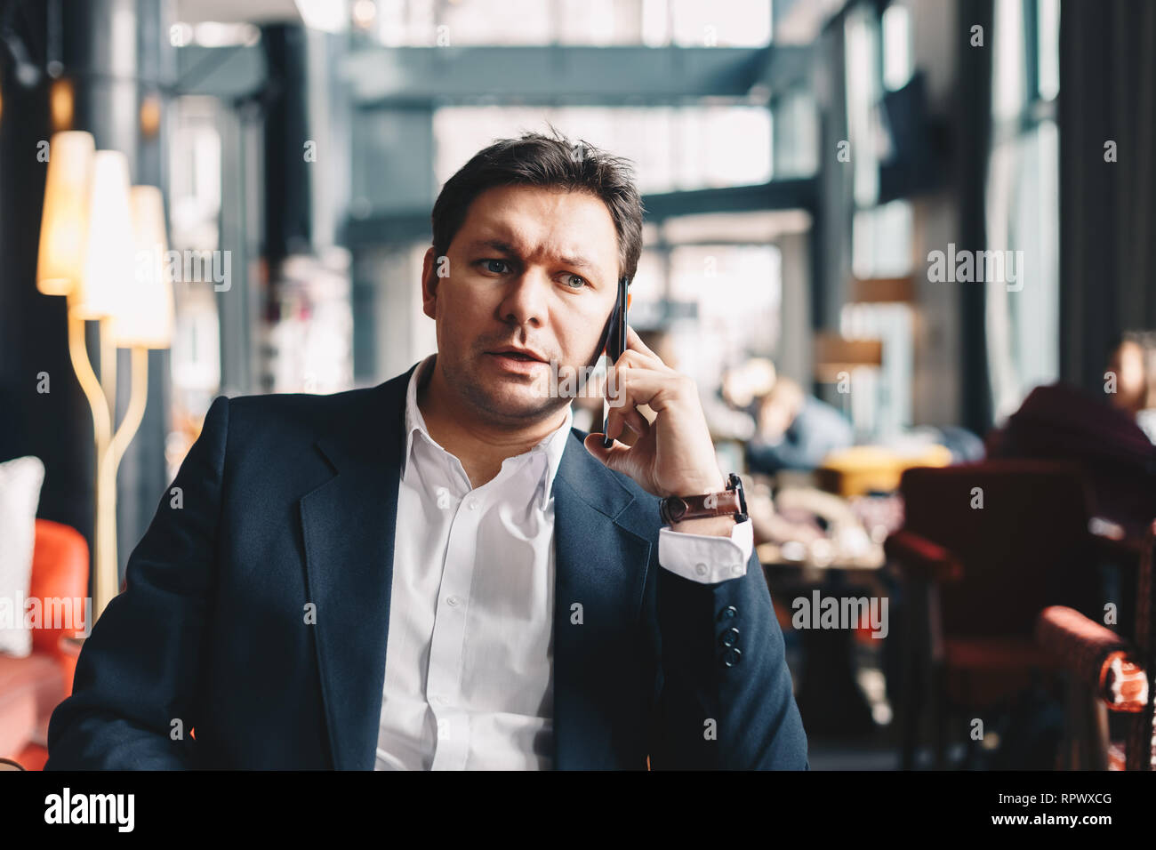 Handsome young businessman in his thirties sitting in a cafe bar during a break from work, talking finance by using a mobile phone. Concept of working - Stock Image