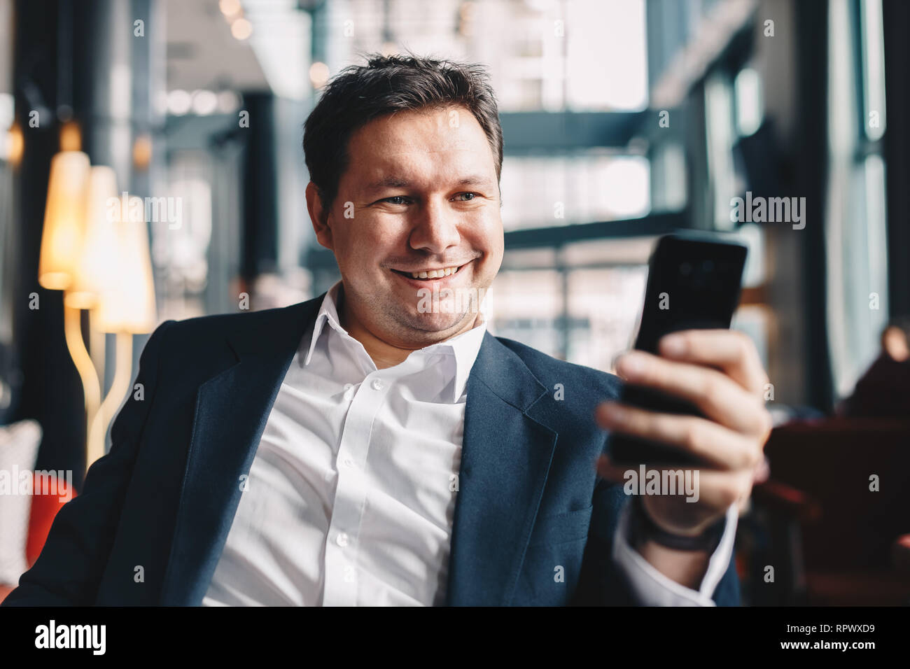 Close-up of attractive young businessman taking a selfie while sitting in a cafe bar during a break from work, smiling and looking at the camera on hi - Stock Image