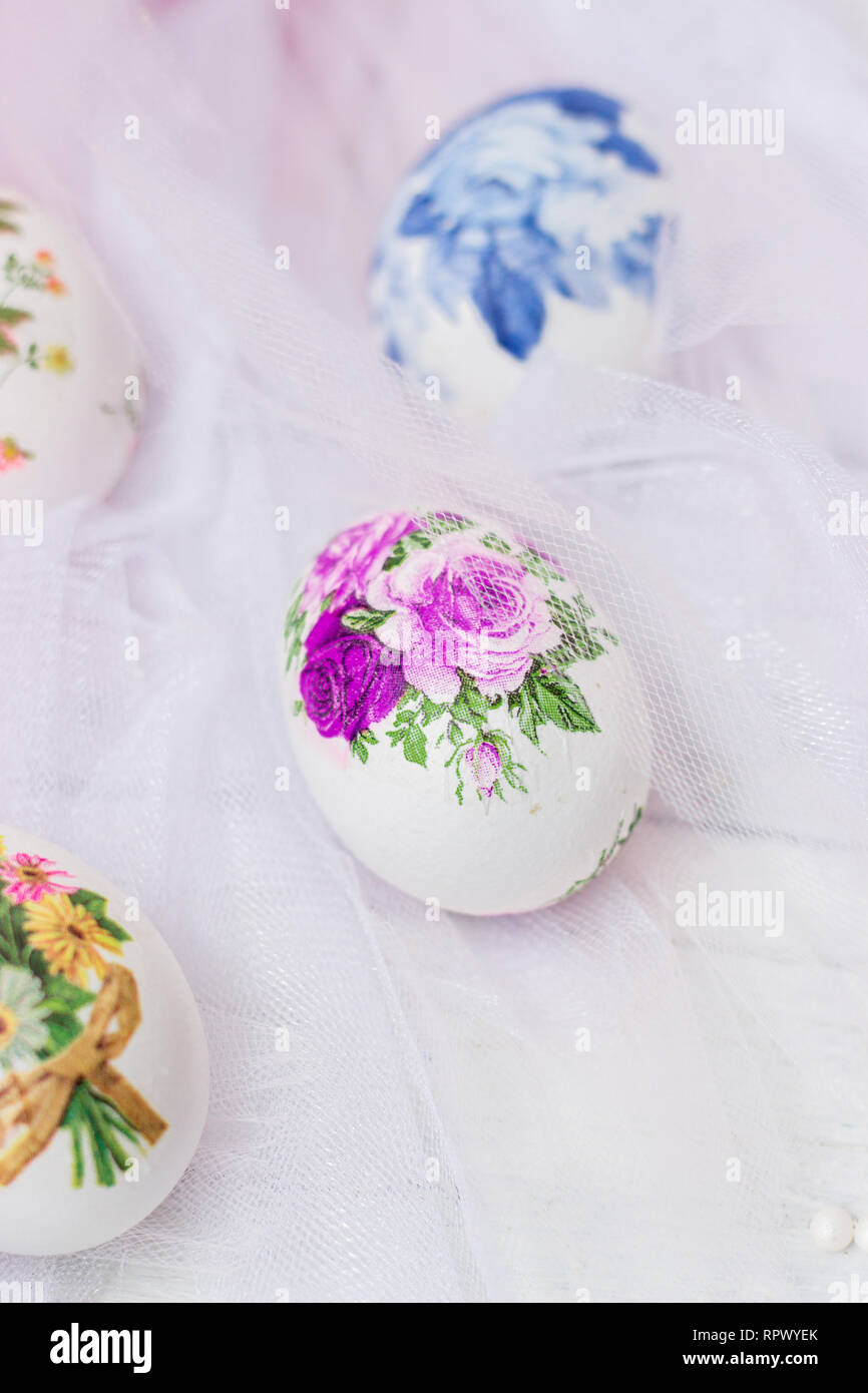Decorated Easter eggs and flowers on white tulle background; decoupage technique Stock Photo