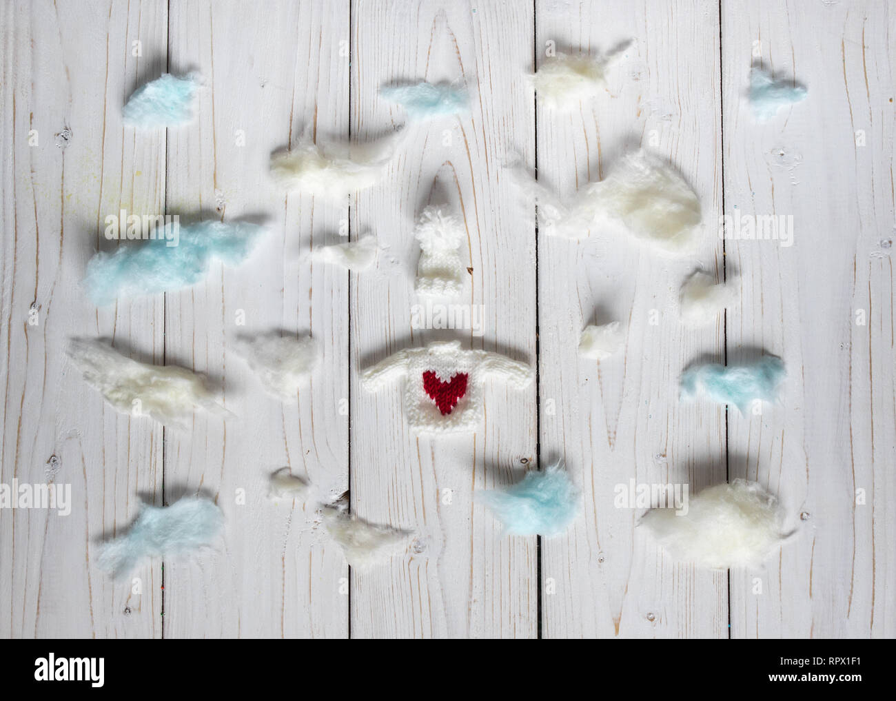 Winter clothes among the clouds, on the white background - Stock Image