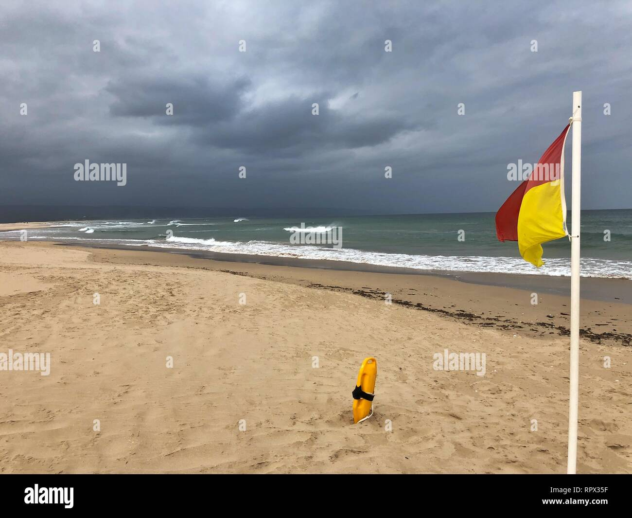 Lifeguard on patrol flags and a rescue buoy, Lookout Beach, Plettenberg Bay, Western Cape, South Africa Stock Photo