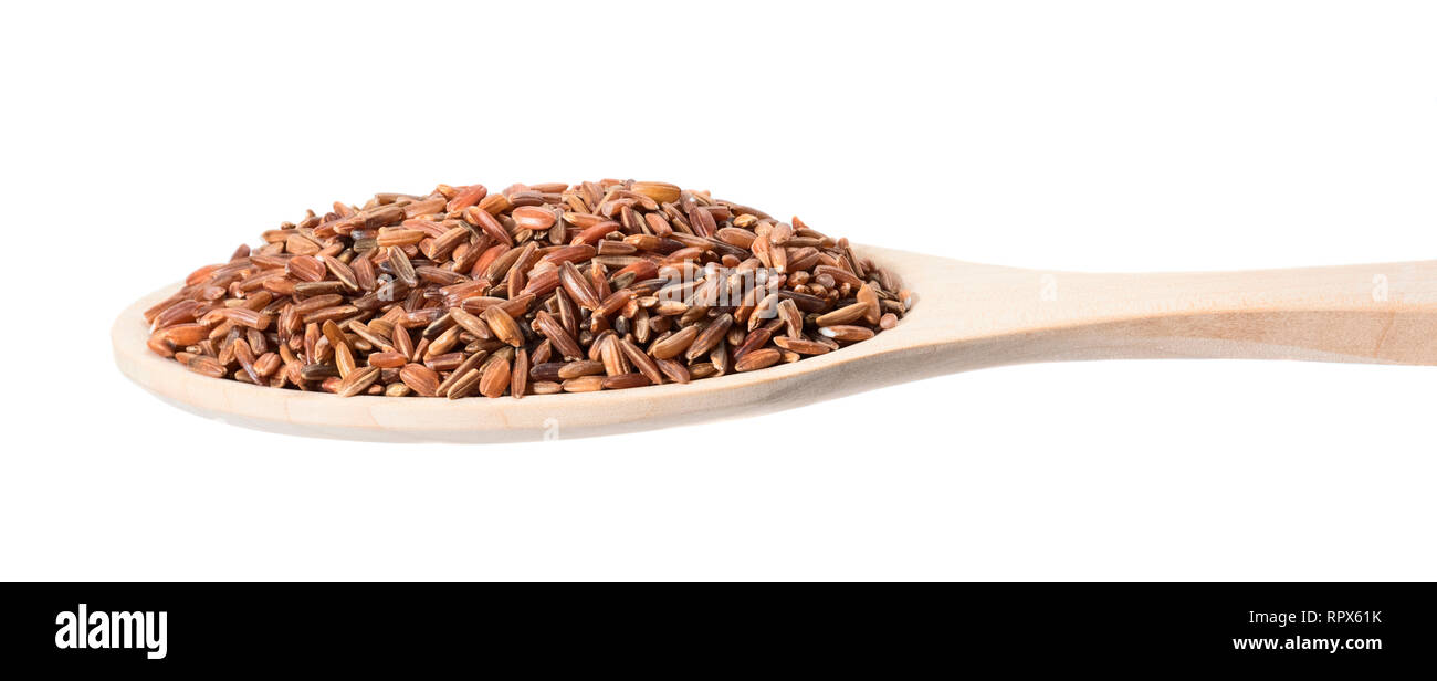 Brown rice in a wooden spoon on a white background - Stock Image