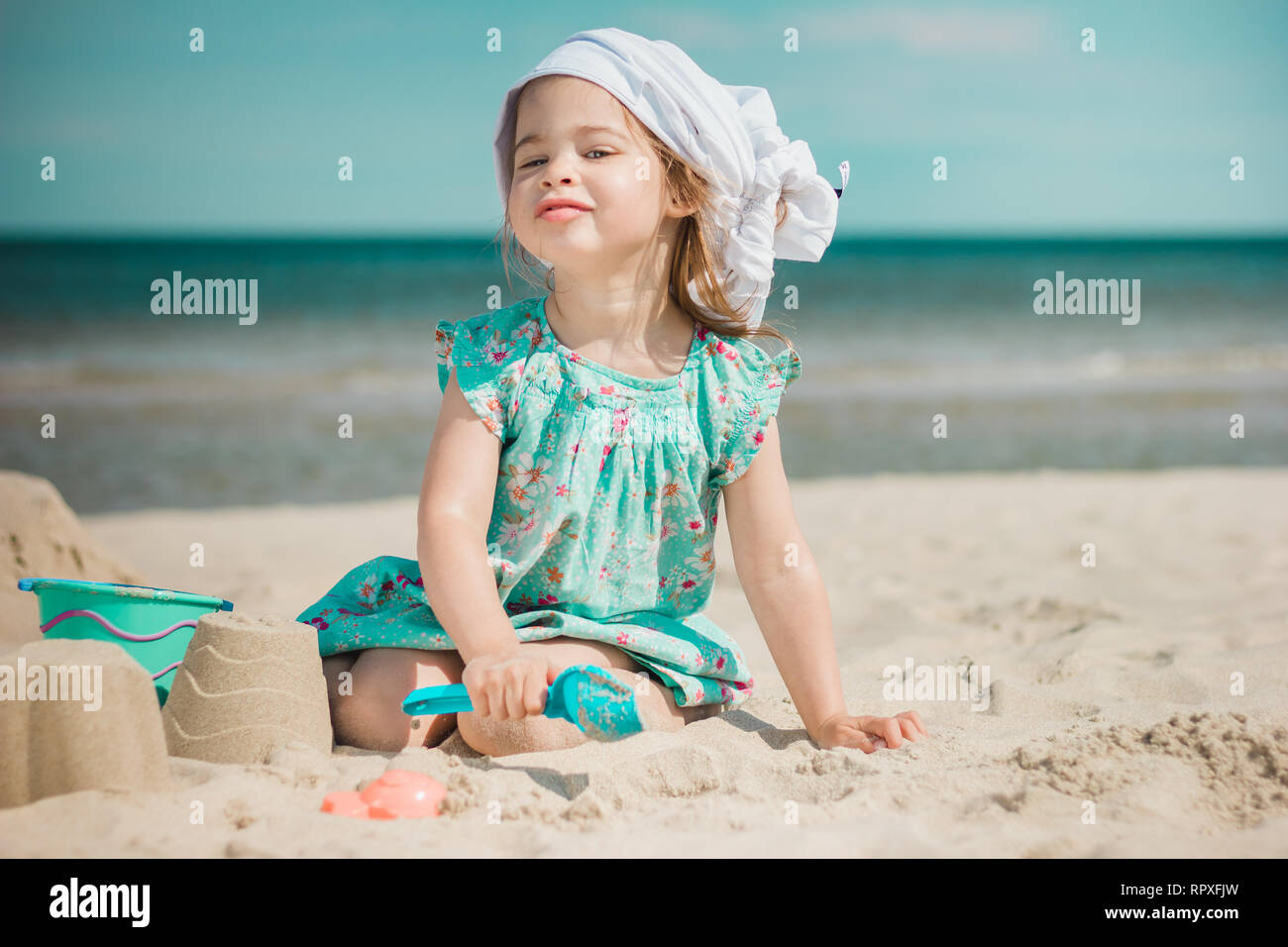 Young girl in sundress making sandcastles on sunny beach. Stock Photo