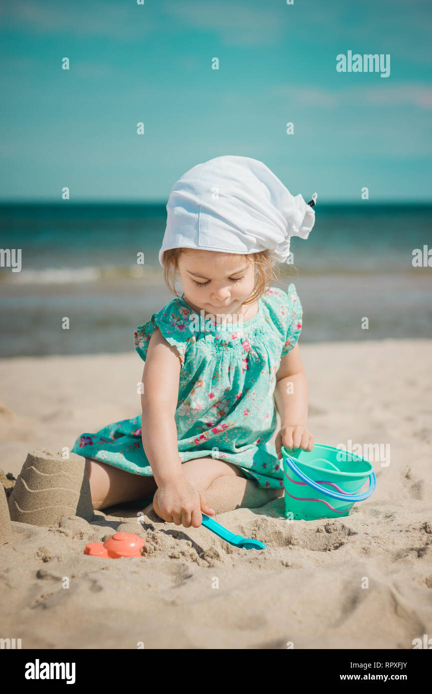 Young girl in sundress making sandcastles on sunny beach. - Stock Image