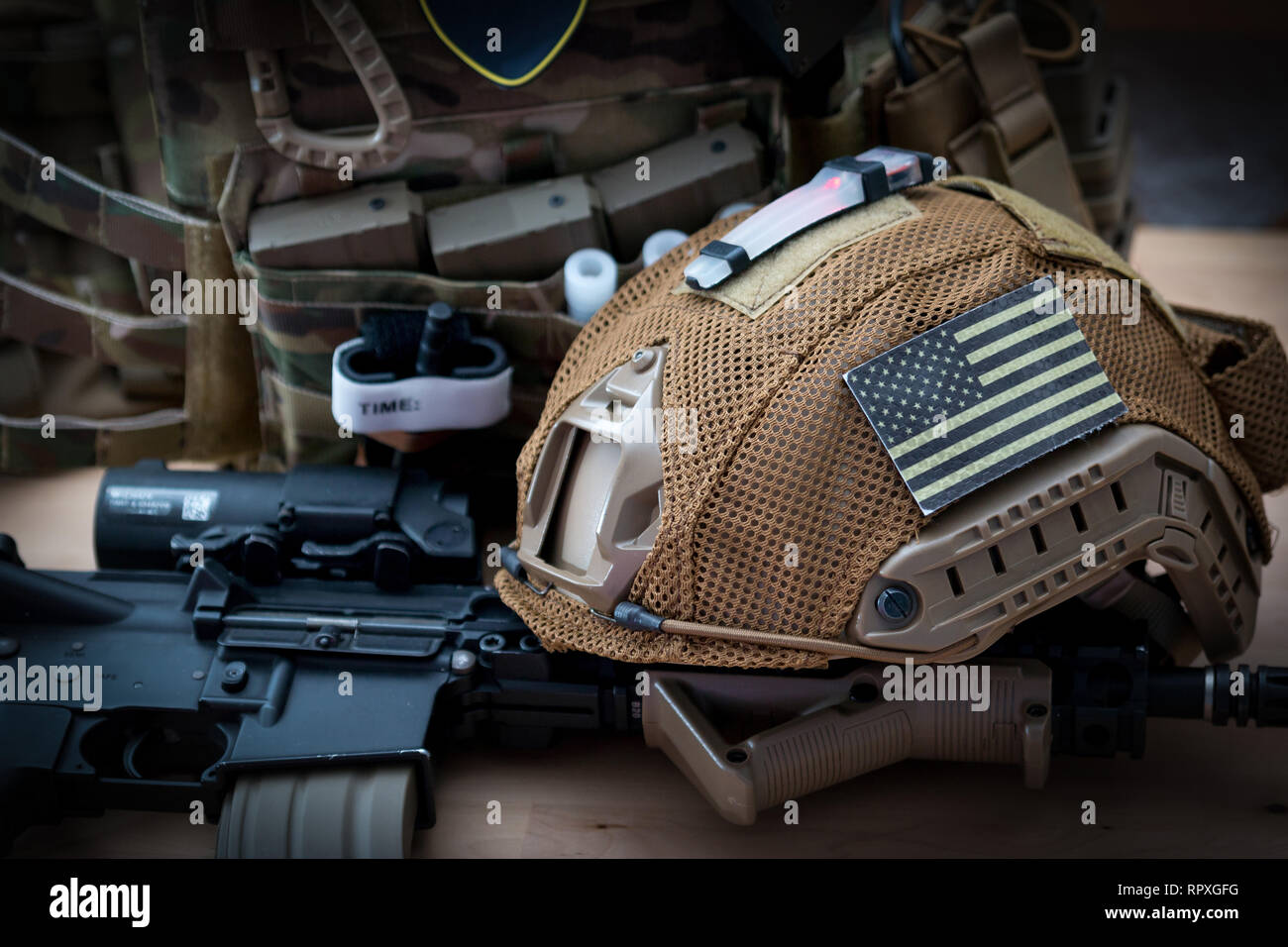 military equipment with a rifle on a wooden table - Stock Image