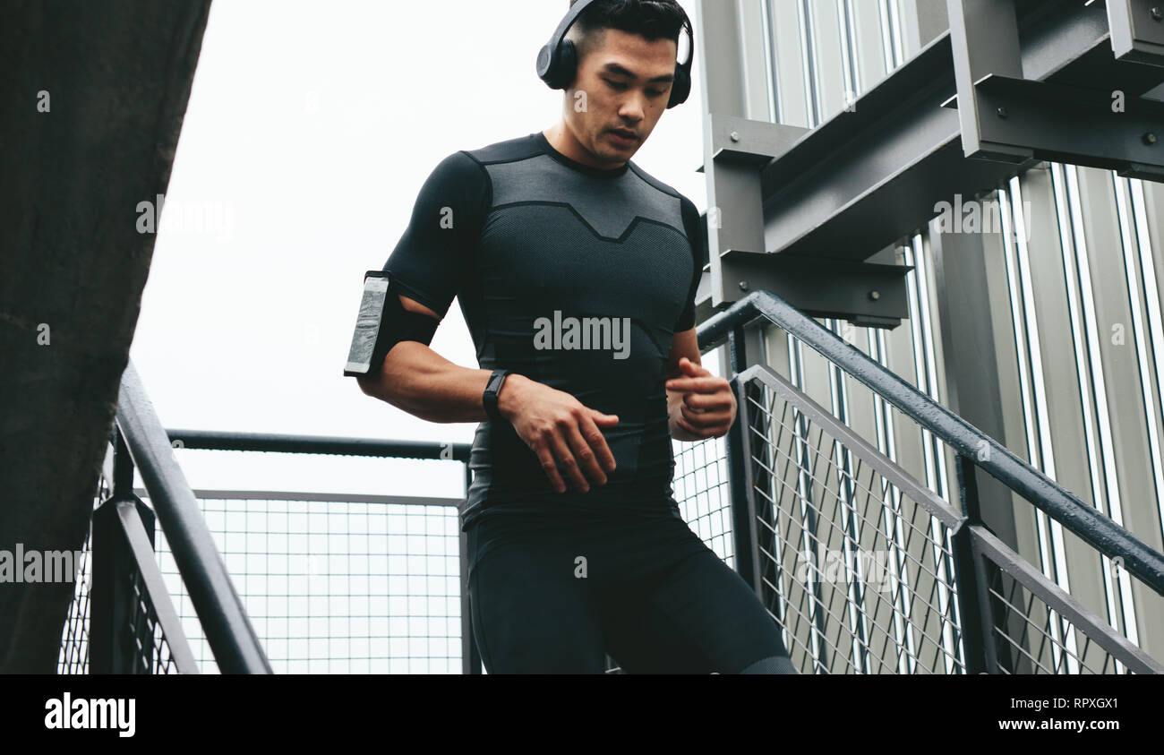 Young man moving down the steps as a part of exercise routine. Young man in sports clothing with headphones and mobile phone armband working out outsi - Stock Image