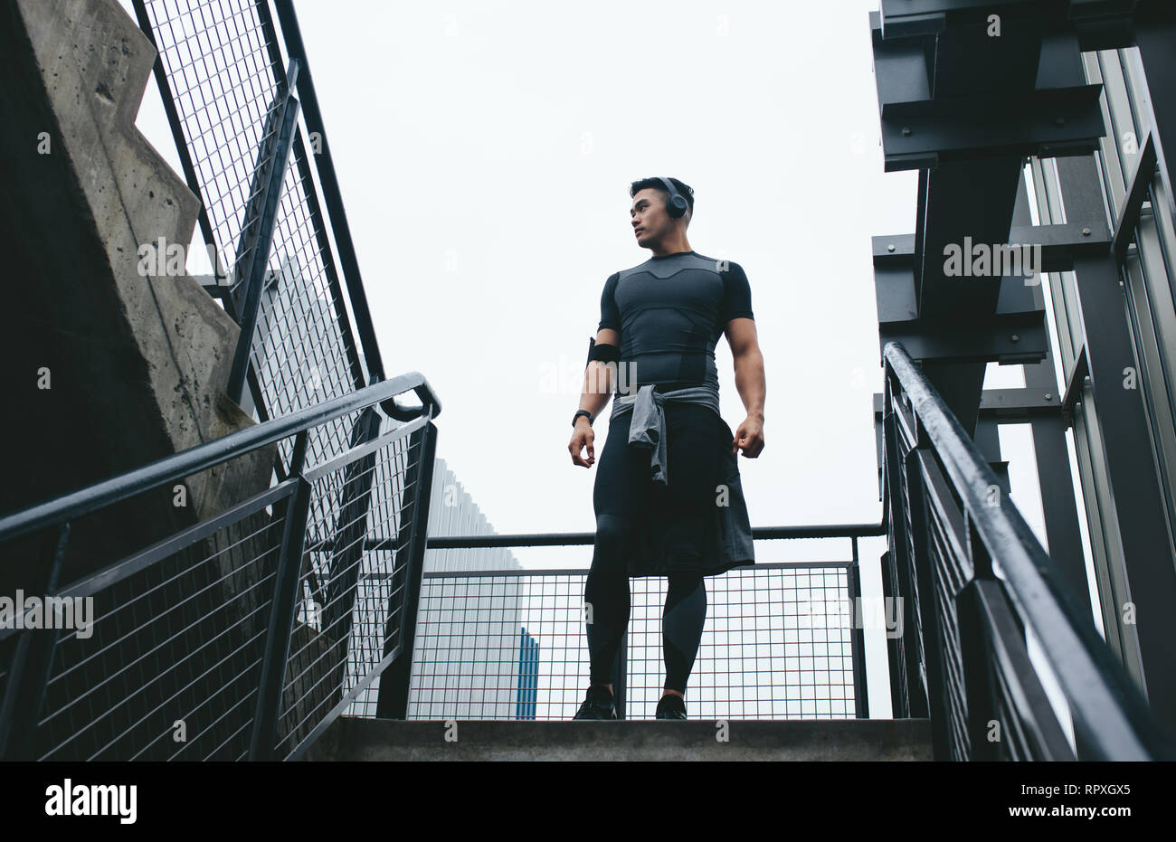 Low angle view of fitness man in sports wear standing on the steps outside. Fit man taking a break during workout. - Stock Image