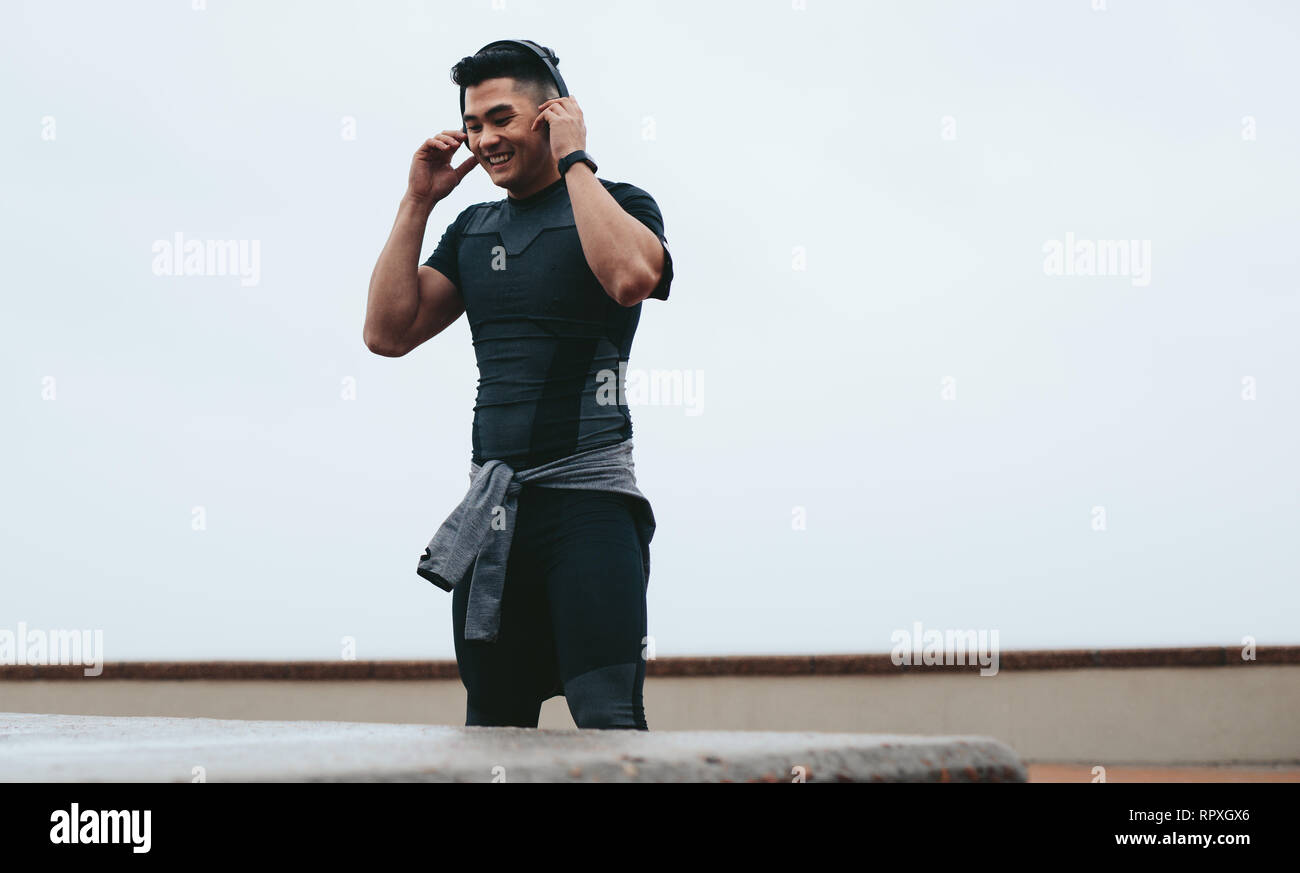 Fit young asian man in sportswear wearing headphone to listen music during outdoor training. Smiling sportsman taking break from training and listenin - Stock Image