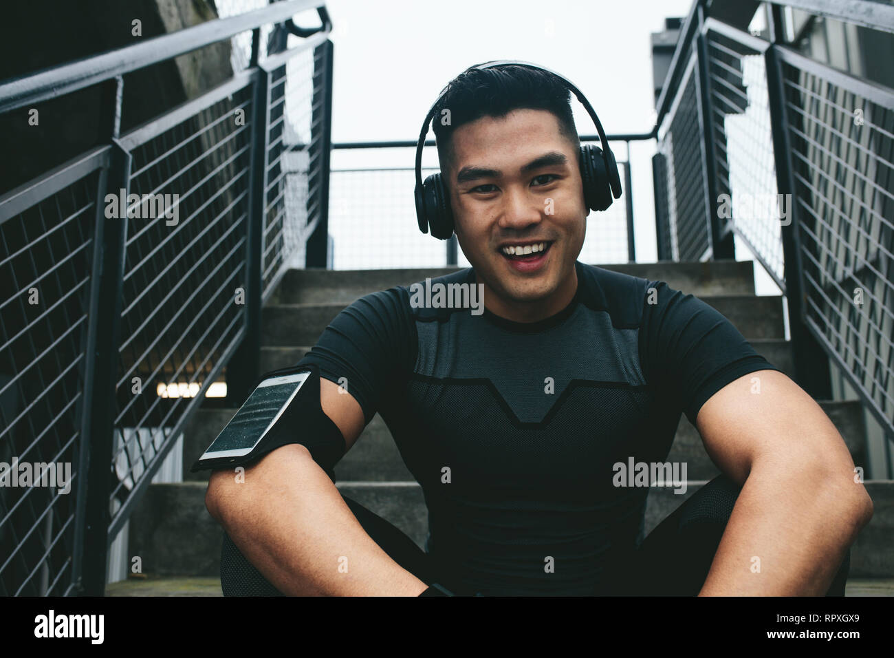 Portrait of laughing asian man sitting on steps with wearing wireless headphones to listening music. Male athlete taking break after training session. - Stock Image