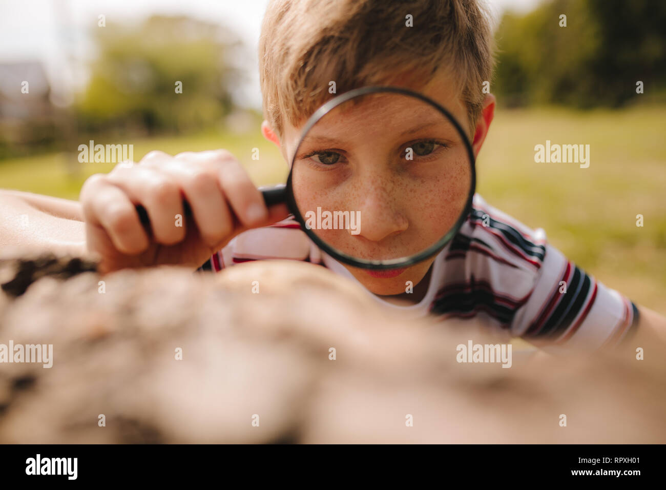 Closeup of cute kid with magnifying glass outdoors. Boy exploring with magnifying glass at the park. - Stock Image