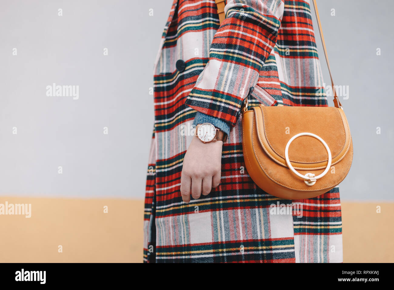 Close-up detail of stylish young woman wearing a coat with tartan pattern and a wrist watch while holding a fancy yellow bag in front of a multicolore - Stock Image