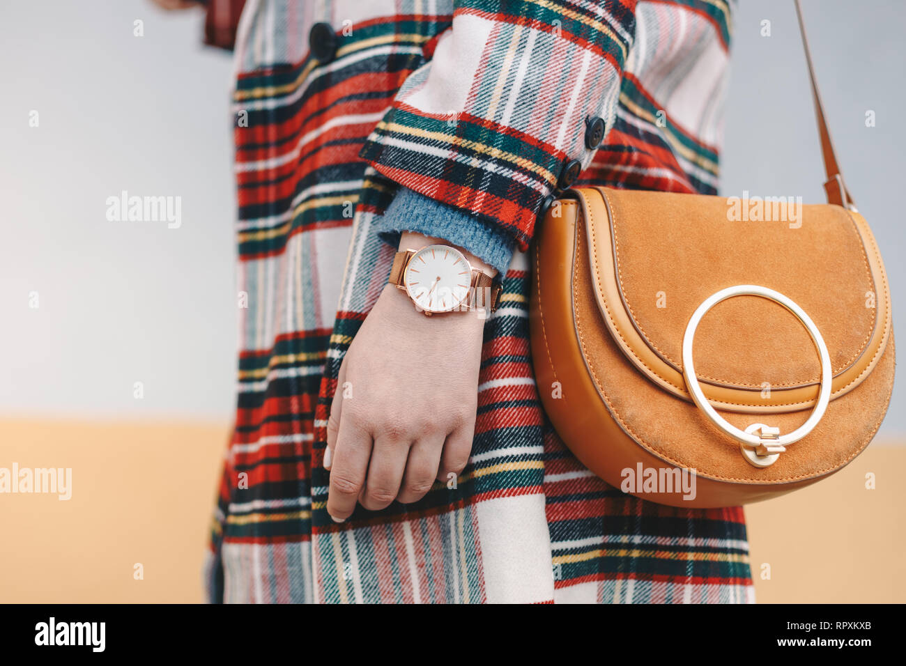 Close up detail of stylish young woman wearing a coat with chequered pattern and a wrist watch while holding a fancy yellow bag in front of a multicol - Stock Image