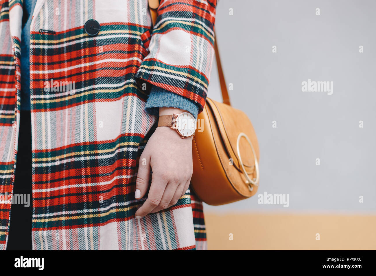 Close up detail of stylish young woman wearing a coat with tartan pattern and a wrist watch while holding a fancy yellow bag in front of a multicolore - Stock Image