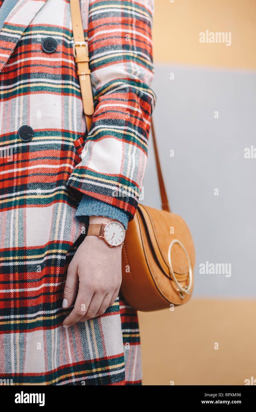 Close up of stylish young woman wearing a coat with tartan pattern and a watch while holding a fancy yellow bag in front of multicolored background. V - Stock Image