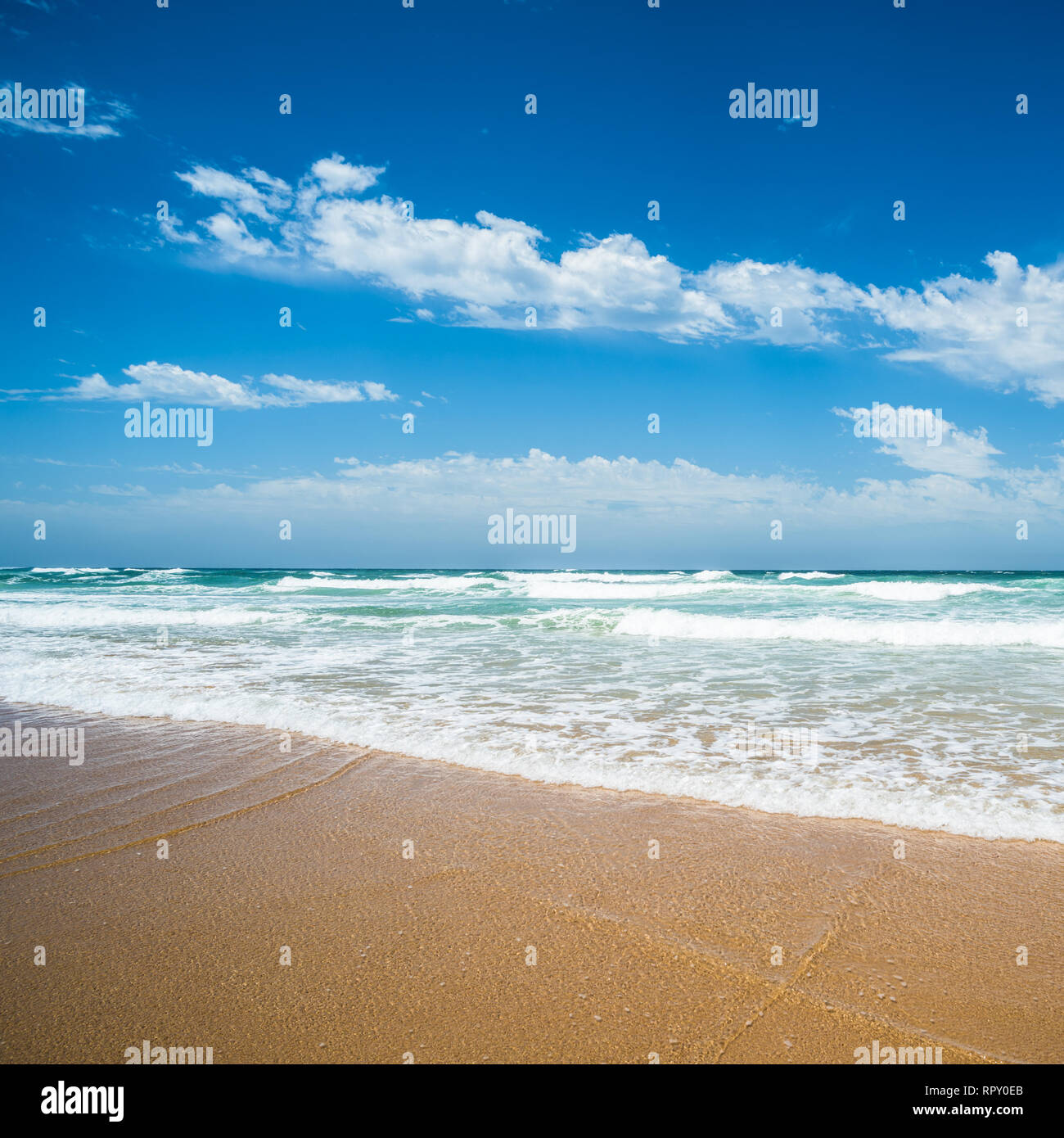 Yellow sand beach, sea and deep blue sky. - Stock Image