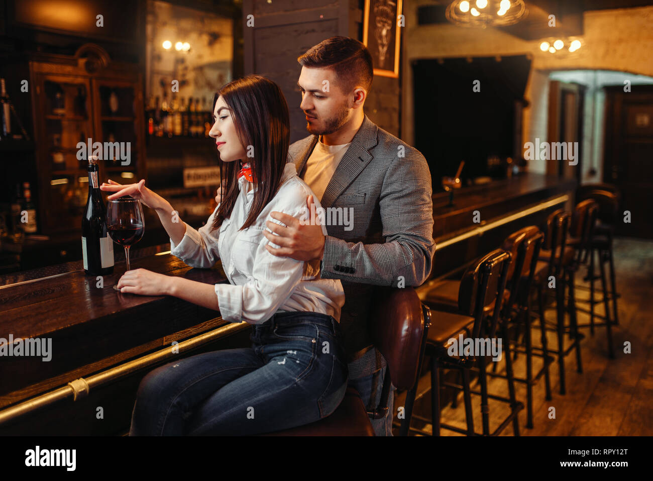 Man and woman relax, couple at wooden bar counter. Lovers leisures in pub, husband and wife relaxing together in nightclub - Stock Image