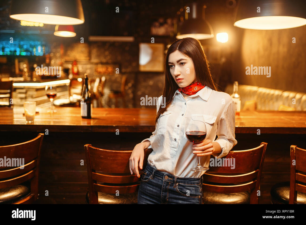 Young attractive woman with glass of red wine at wooden bar counter. Female customer leisures in pub - Stock Image