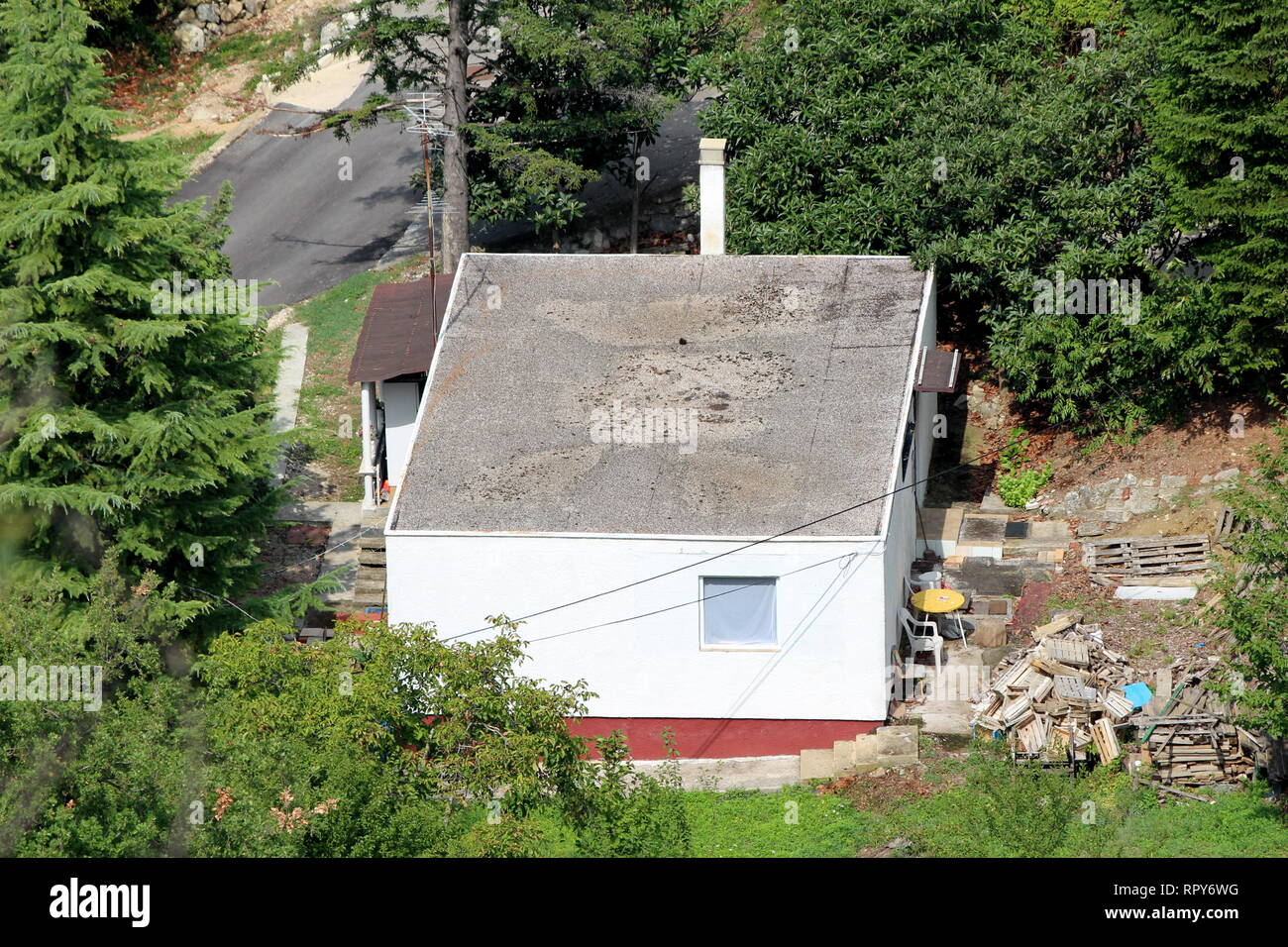 Top View Of Small Ground Floor Family House With Flat Roof And Construction Material In Backyard Surrounded With Dense Forest And Paved Road Stock Photo Alamy
