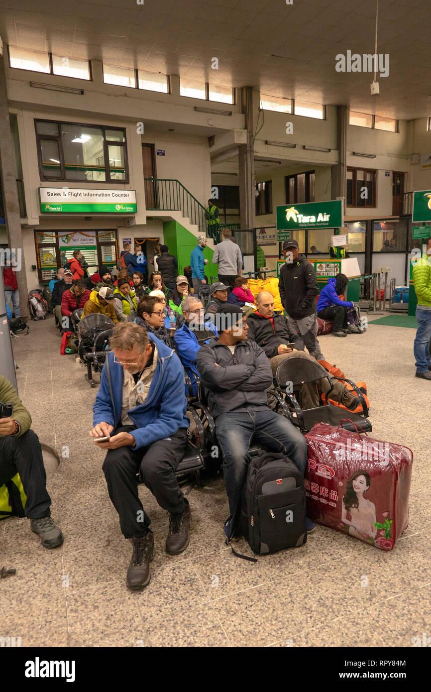 Nepal, Kathmandu, Tribhuvan International airport, domestic departure area, passengers sat waiting for delayed flights to Lukla - Stock Image