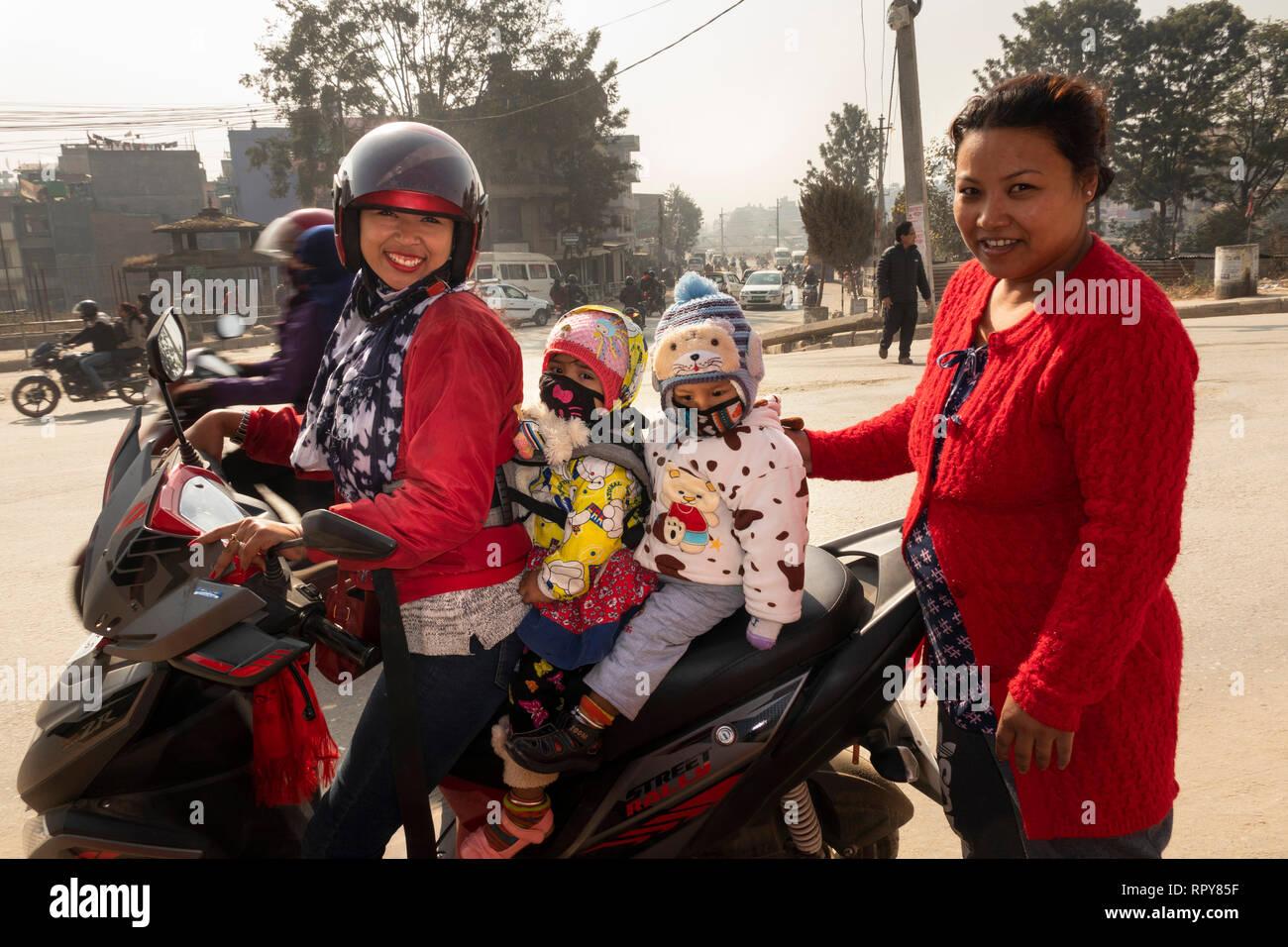 Nepal, Kathmandu, Thamel, Swayambhu Marg, woman carrying two young children on motorbike, outside Indrani and Mahadev temples - Stock Image