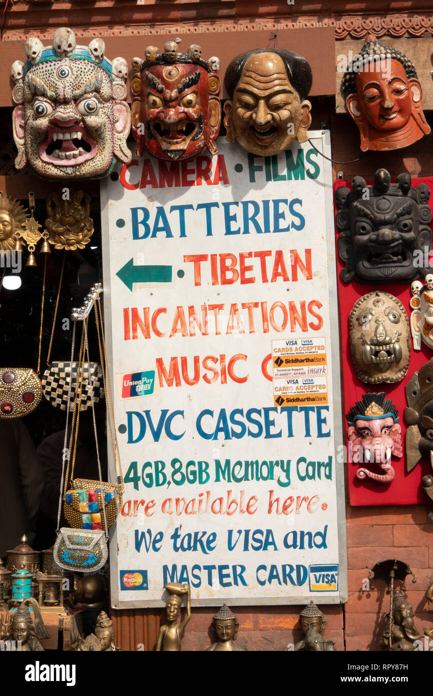 Nepal, Kathmandu, Swayambhunath Temple, sign advertising modern tourist's supplies for sale amongst antique and modern reproduction Buddhist artifacts - Stock Image