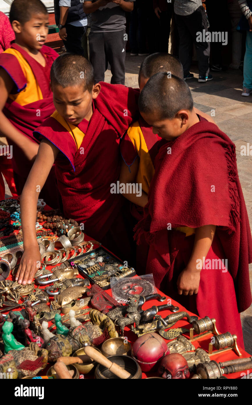 Nepal, Kathmandu, Swayambhunath Temple, three child monks looking at antique and modern reproduction Buddhist artifacts for sale on stall - Stock Image