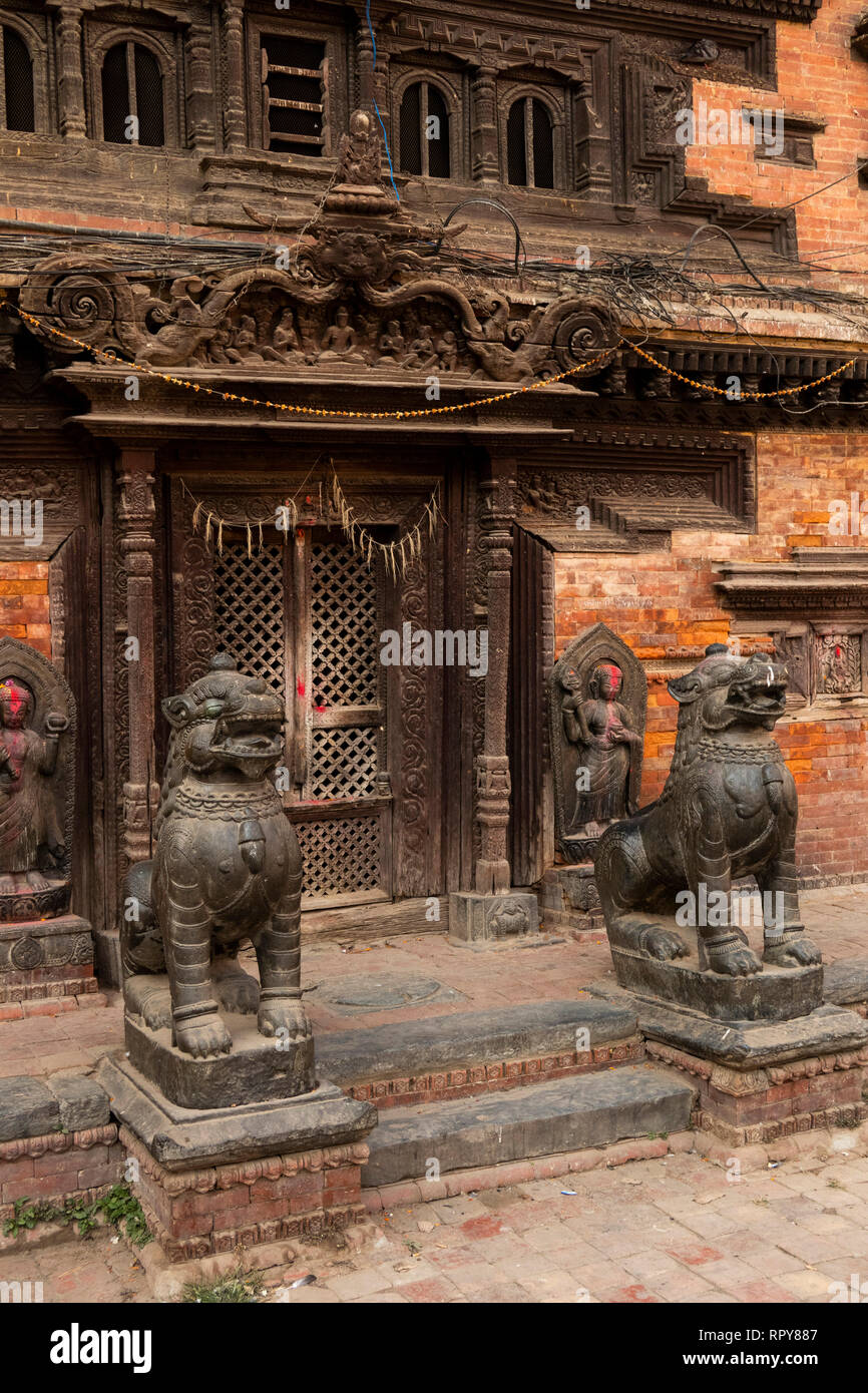 Nepal, Kathmandu, city centre, Pyaphal Tole, Yatkha Bahal, ancient carved wooden temple entrance to courtyard, guarded by bronze lion statues - Stock Image
