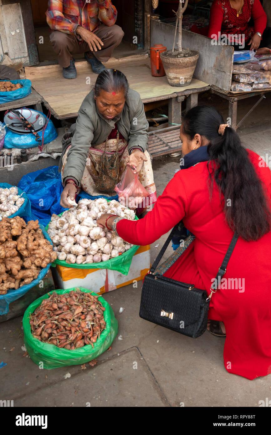 Nepal, Kathmandu, city centre, Asan Tole, old Nepali woman, selling garlic, onions and ginger from street stall - Stock Image