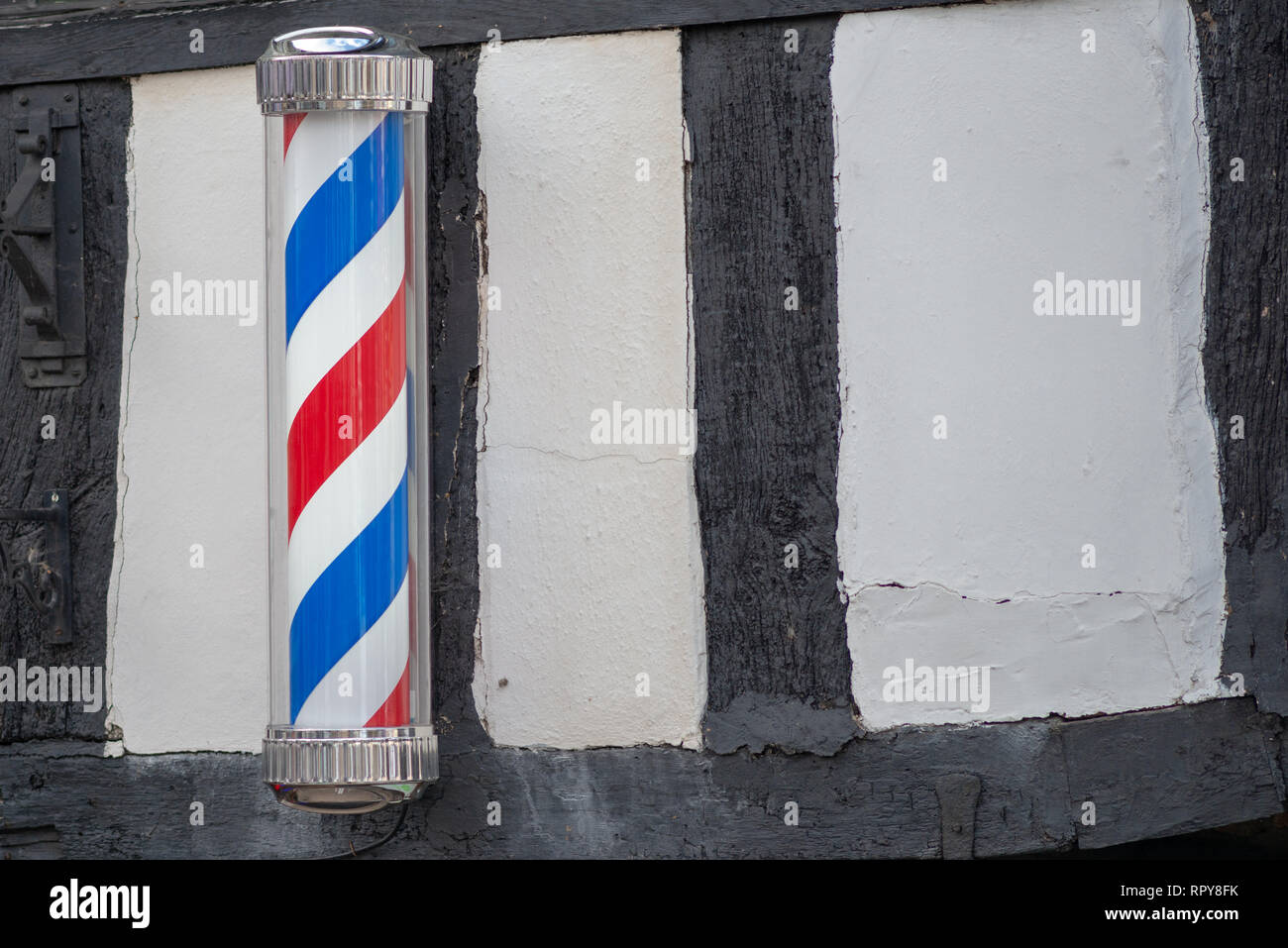 red white and blue barbers pole on ancient timber wall in the UK - Stock Image