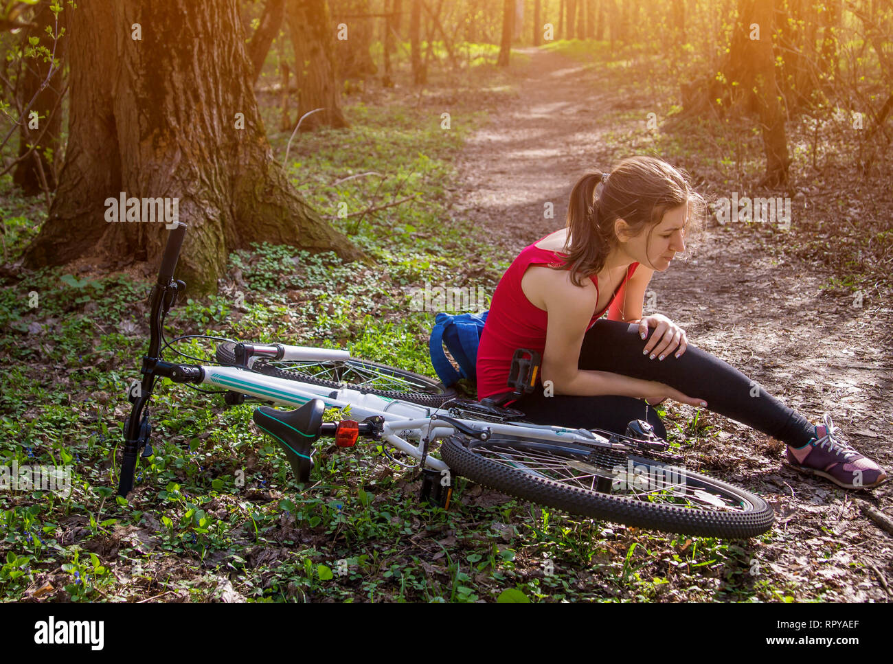 Young woman fell off the bicycle and hurt knee in forest. Injuries and traumas during sport - Stock Image