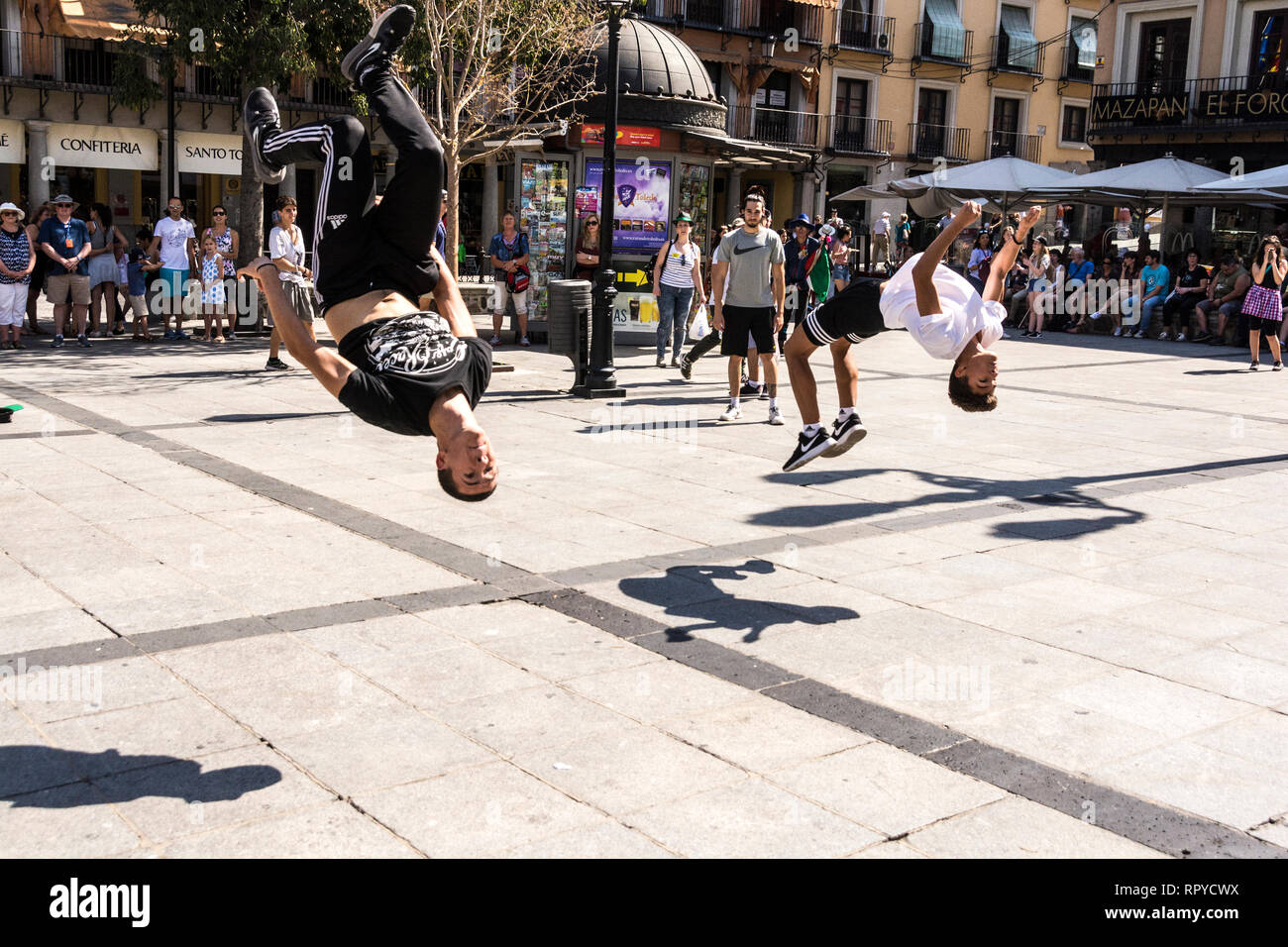 Two young teenagers doing gymnastics for extra money, Granada, Spain. - Stock Image