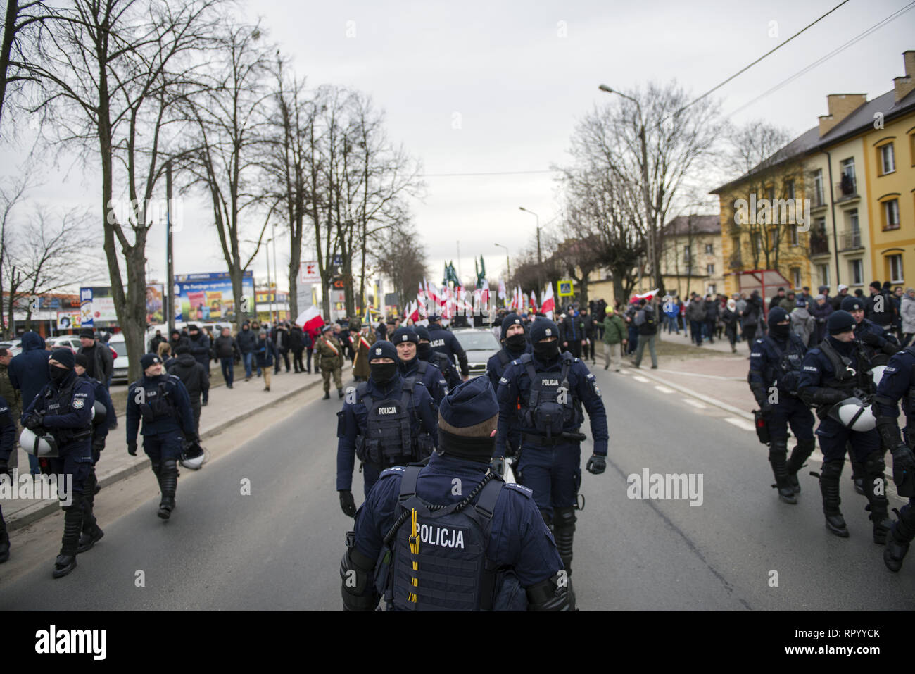 Hajnowka, Poldlaskie, Poland. 23rd Feb, 2019. Police forces seen securing the nationalists on the front during the march.Polish nationalists organized a commemorative march of the 'Cursed Soldiers'' in the city of Hajnowka next to the Belarusian border. The Cursed Soldiers also known as the Doomed Soldiers were anti-communist resistant fighters after WWII, however they were also famous of committing crimes against civilians, mostly ethnic Belarusians. Credit: Attila Husejnow/SOPA Images/ZUMA Wire/Alamy Live News - Stock Image