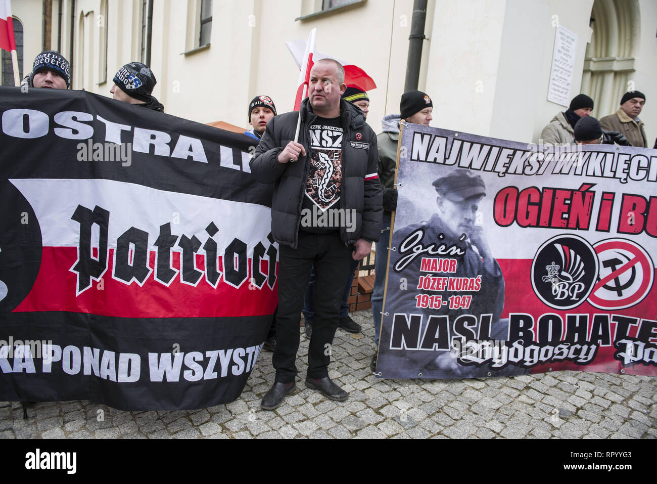 Hajnowka, Poldlaskie, Poland. 23rd Feb, 2019. A man see standing next to banners during commemorative.Polish nationalists organized a commemorative march of the 'Cursed Soldiers'' in the city of Hajnowka next to the Belarusian border. The Cursed Soldiers also known as the Doomed Soldiers were anti-communist resistant fighters after WWII, however they were also famous of committing crimes against civilians, mostly ethnic Belarusians. Credit: Attila Husejnow/SOPA Images/ZUMA Wire/Alamy Live News - Stock Image