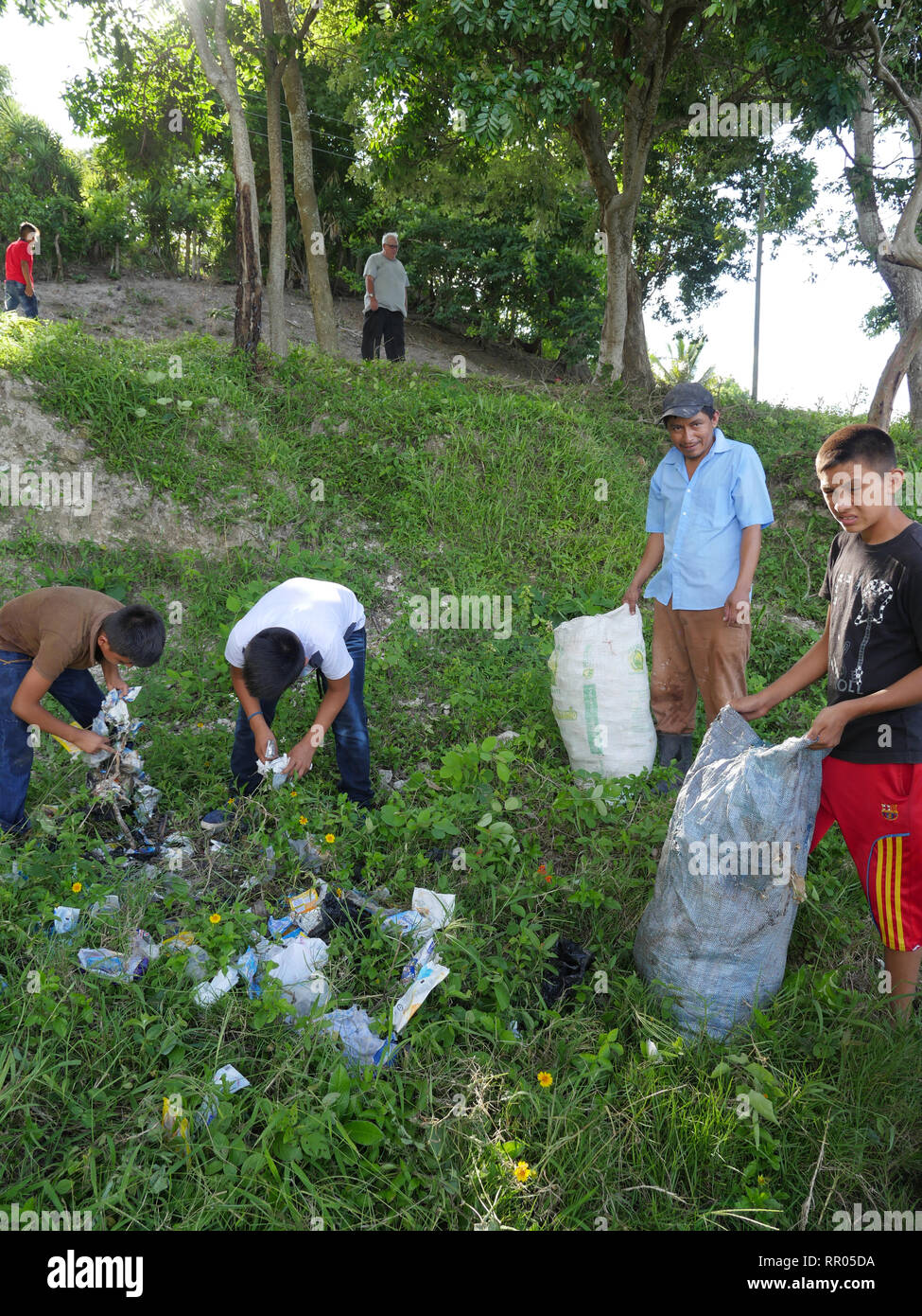 GUATEMALA  Rescue of the natural ecocsystem around Lake Nacanche, near El Remate, Peten. The Remate Parish Leadership and Formation team picking up litter, especially plastic, from the lake. Local children recruited to help with the clean-up operation. - Stock Image