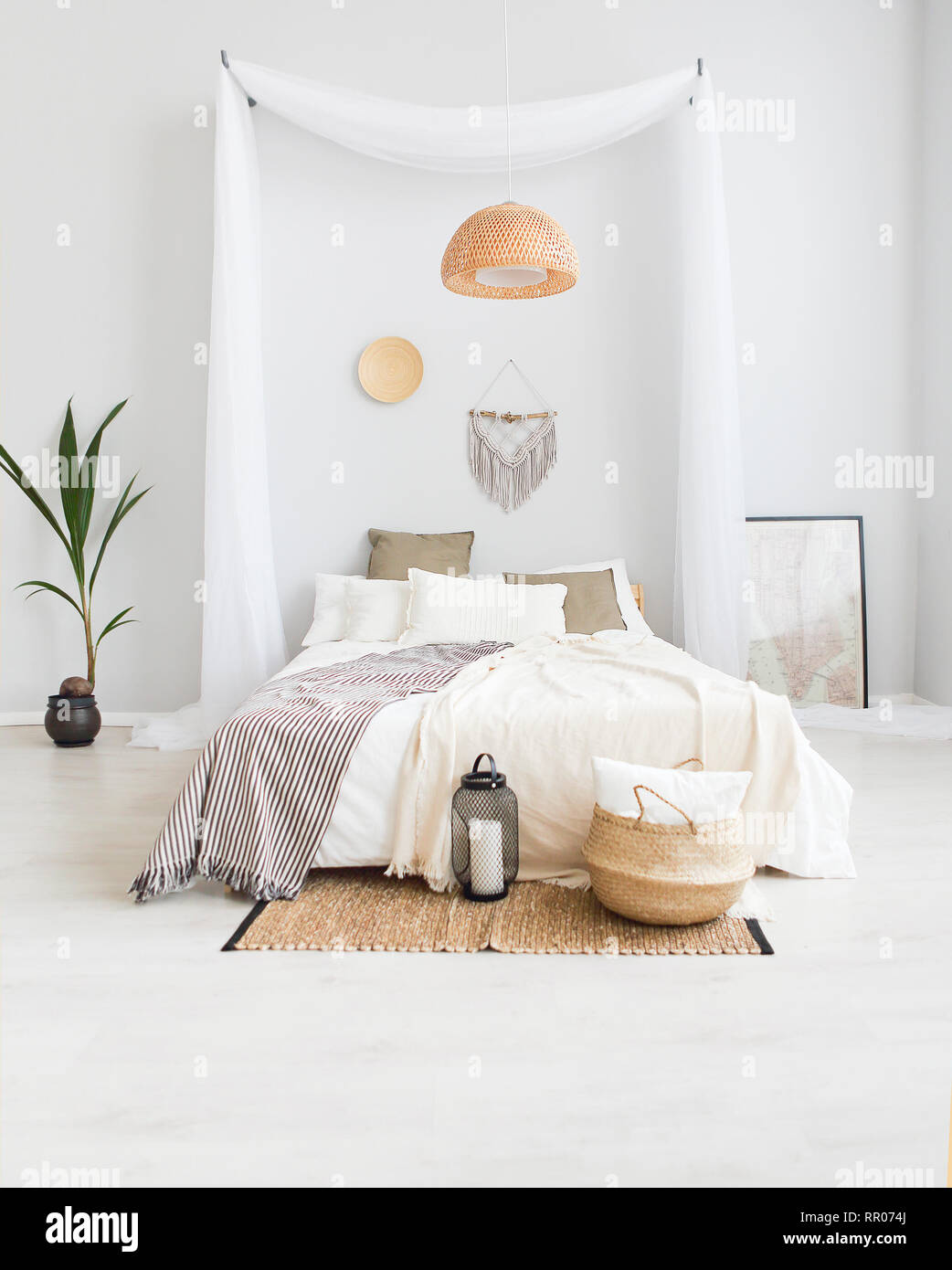 White and beige bedroom in boho style with macrame on the ...