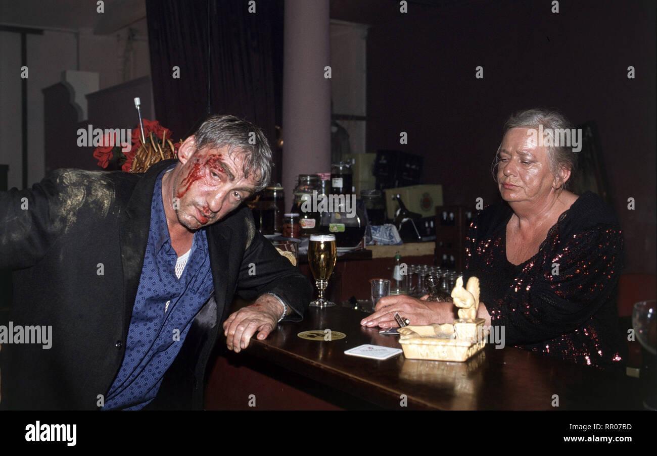 TÖDLICHES NETZ / D 1993 / Vivian Naefe Nach der Schlägerei trinkt Beckmann (GOTTFRIED JOHN) erstmal ein Bier. Foto: Szene mit GUDRUN OKRAS als Wirtin. 38249 / Überschrift: TÖDLICHES NETZ / D 1993 Stock Photo