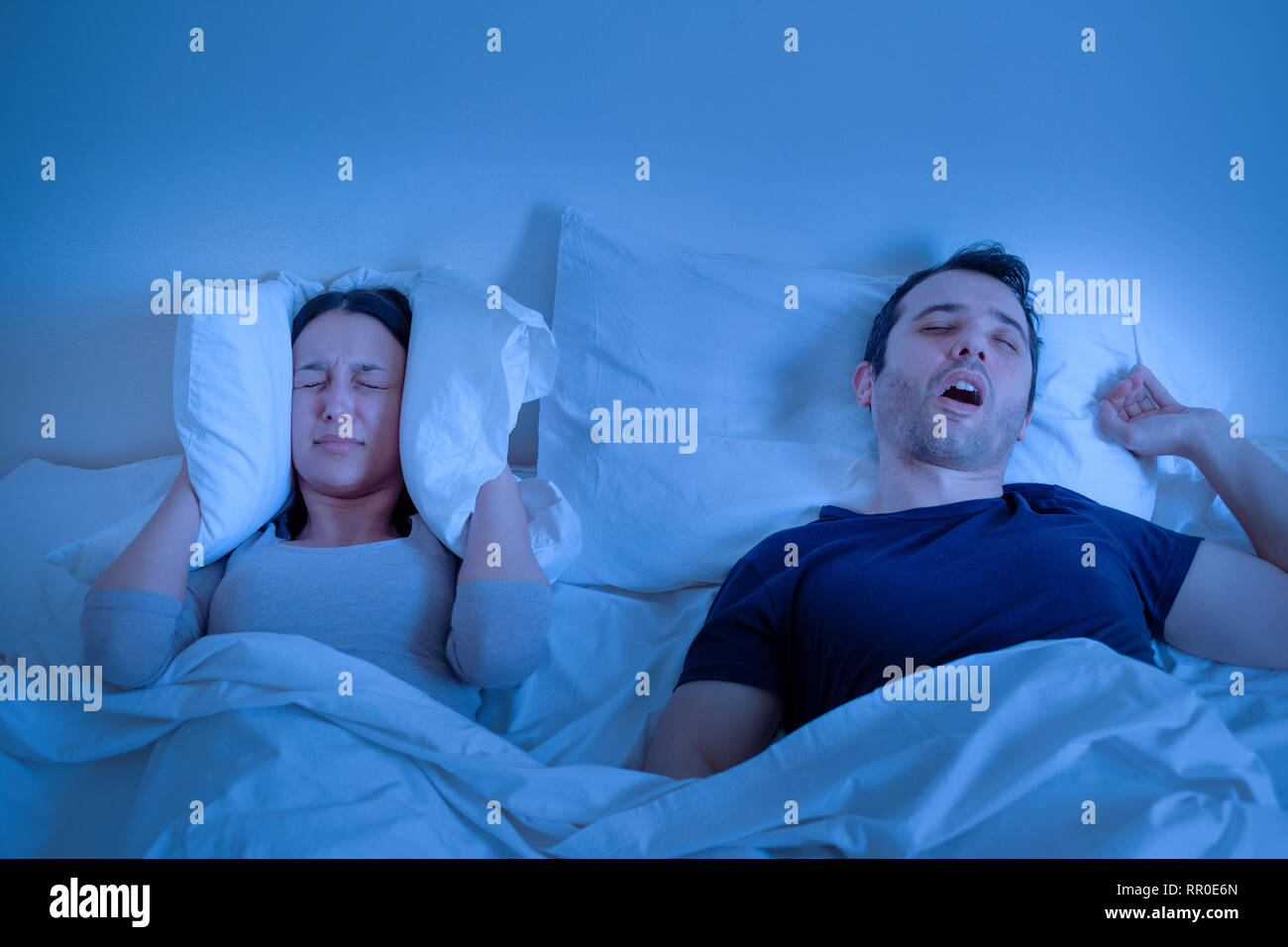 Relationship problem and husband snoring in bed loudly - Stock Image