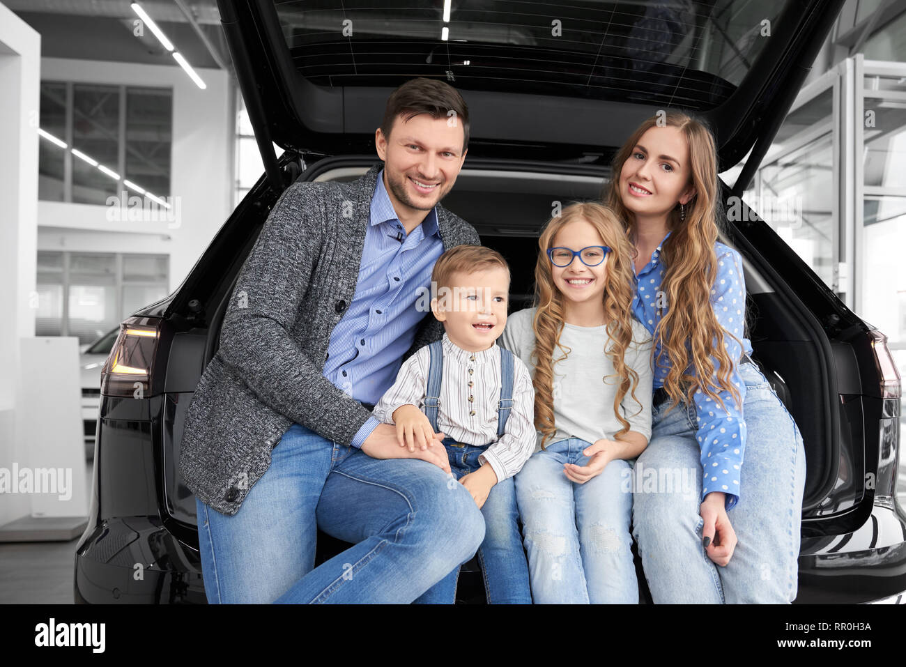 Cheerful and happy family posing together in car center showroom. Parents and children sitting in car trunk, luggage space of black automobile looking at camera and smiling. - Stock Image