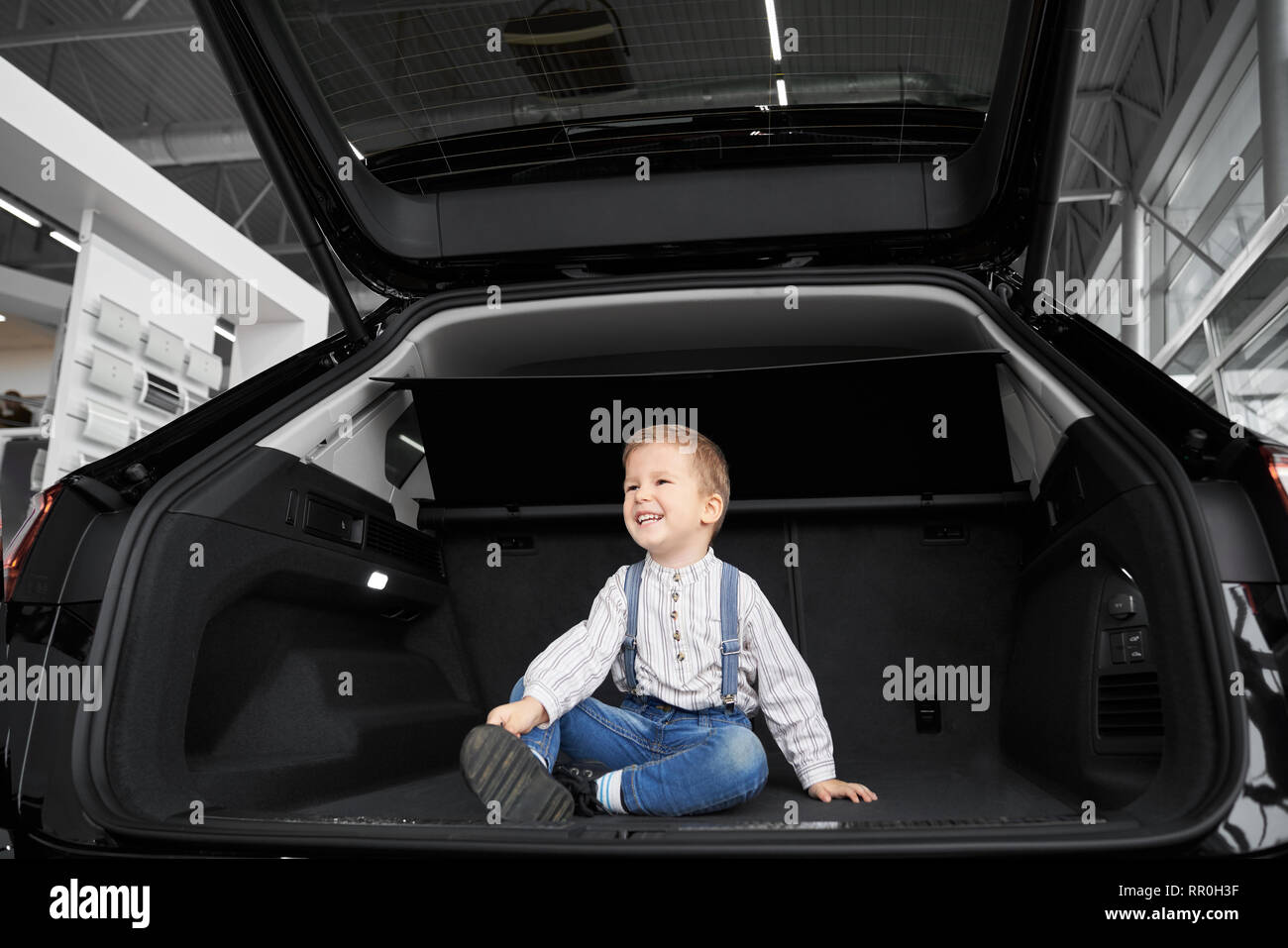 Handsome, cute little boy sitting in luggage space of big, new black automobile. Pretty child posing, looking away and smiling. Happy kid observing vehicle in car trunk. - Stock Image